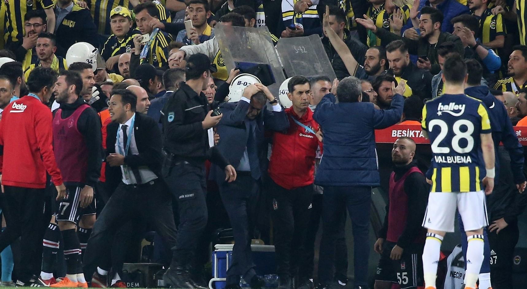 Besu0327iktasu0327 head coach Su0327enol Guu0308nesu0327 (C) holds his head after being hit by an object during the Ziraat Turkish Cup semi final second leg match between Fenerbahcu0327e and Besu0327iktasu0327 at Fenerbahcu0327e stadium in Istanbul.
