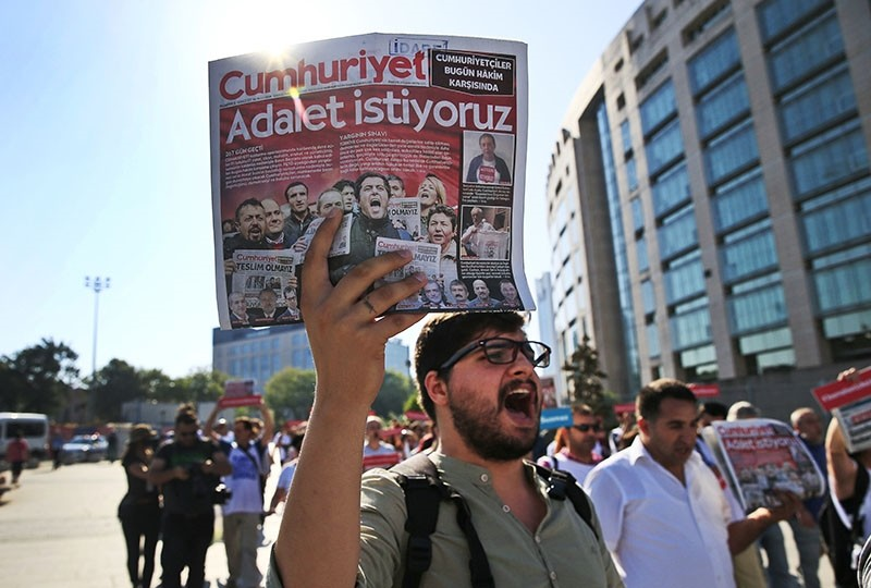 Activists, one holding today's copy of the Cumhuriyet newspaper, march to the court in Istanbul, Monday, July 24, 2017. The newspaper headline reads in Turkish: ,We want justice., (AP Photo)