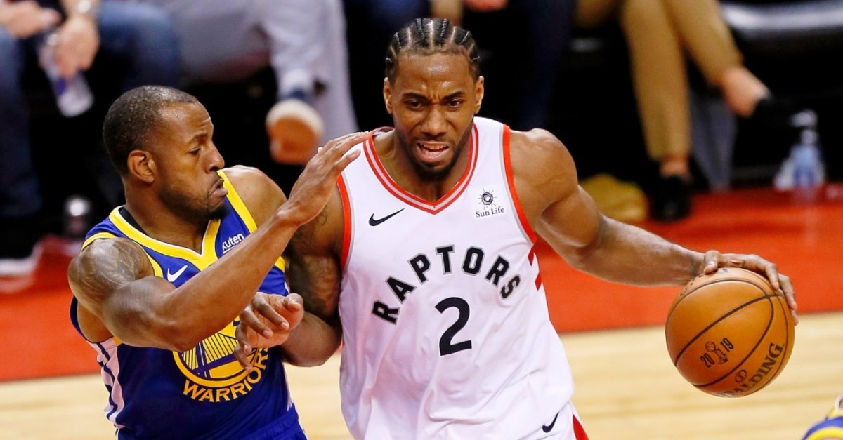 Kawhi Leonard dribbles against Andre Iguodala during the third quarter in game five of the NBA Finals June 11, 2019.