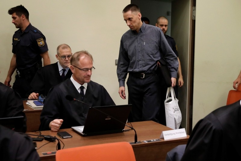 In this June 5, 2018 file photo defendant Ralf Wohlleben, center with white bag, arrives for his trial and the trial against terror suspect Beate Zschaepe in the court room in Munich, Germany. (AP Photo)