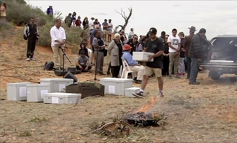 In this image made from video, the oldest human remains in a coffin are placed on the ground for a traditional ceremony in Lake Mungo, Australia, Friday, Nov. 17, 2017. (AP Photo)