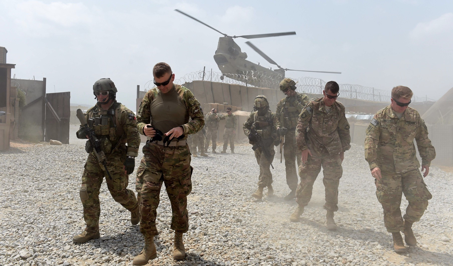 U.S. army soldiers walk as a NATO helicopter flies overhead at coalition force, in the Khogyani district, eastern Syria, Aug. 12, 2015.