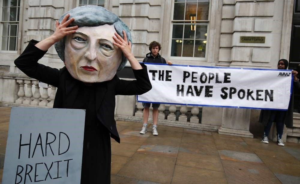 A demonstrator wears a mask depicting Britain's Prime Minister and leader of the Conservative Party Theresa May, and poses with a mock gravestone bearing the words ,Hard Brexit, RIP.,