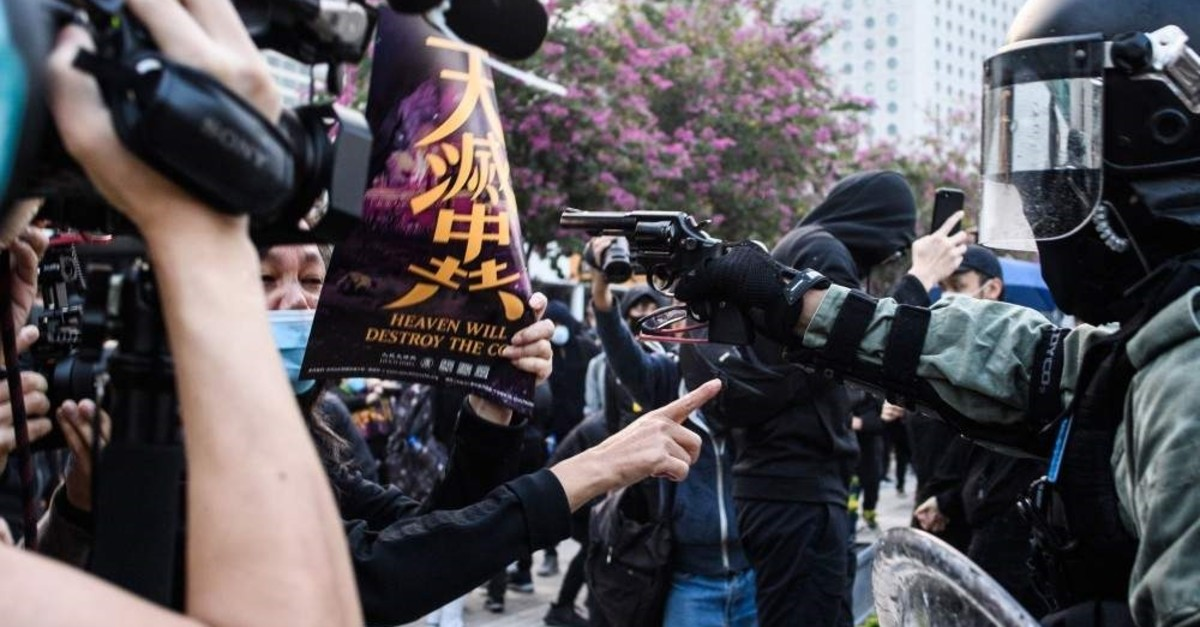 A police officer points a pistol during a rally in Hong Kong on Dec. 22, 2019, to show support for the Uighur minority in China. (AFP Photo)