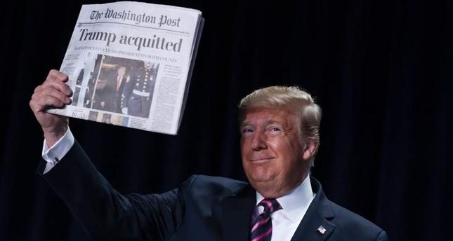 President Donald Trump holds up a newspaper during the 68th annual National Prayer Breakfast, at the Washington Hilton, Thursday, Feb. 6, 2020, in Washington. AP Photo/ Evan Vucci
