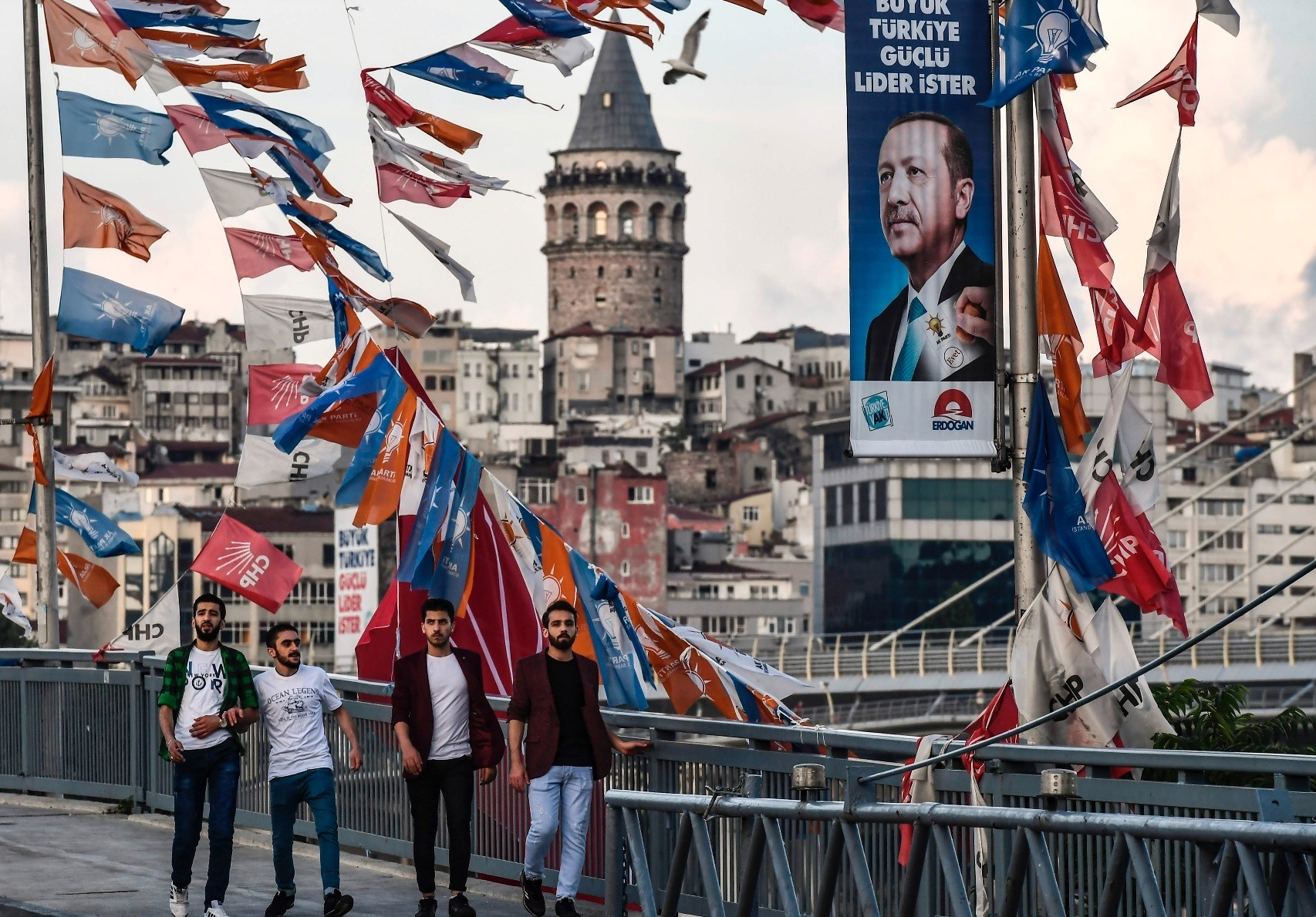 Onlookers pass by party campaign banners and a portrait of President Erdou011fan for the upcoming elections, Istanbul, June 18.