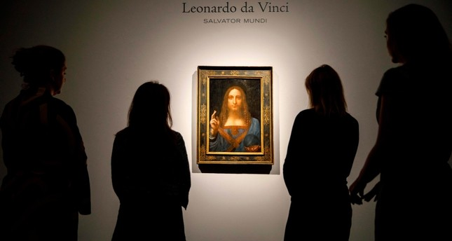 In this file photo taken on October 22, 2017 Christie's employees pose in front of a painting entitled Salvator Mundi by Italian polymath Leonardo da Vinci at a photocall at Christie's auction house in central London. (AFP Photo)