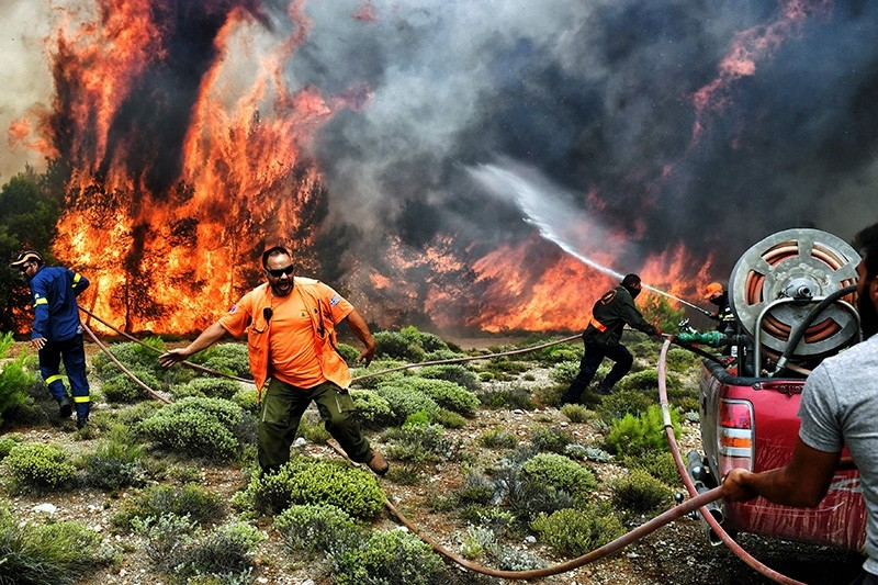 Firefighters and volunteers try to extinguish flames during a wildfire at the village of Kineta, near Athens, on July 24, 2018.