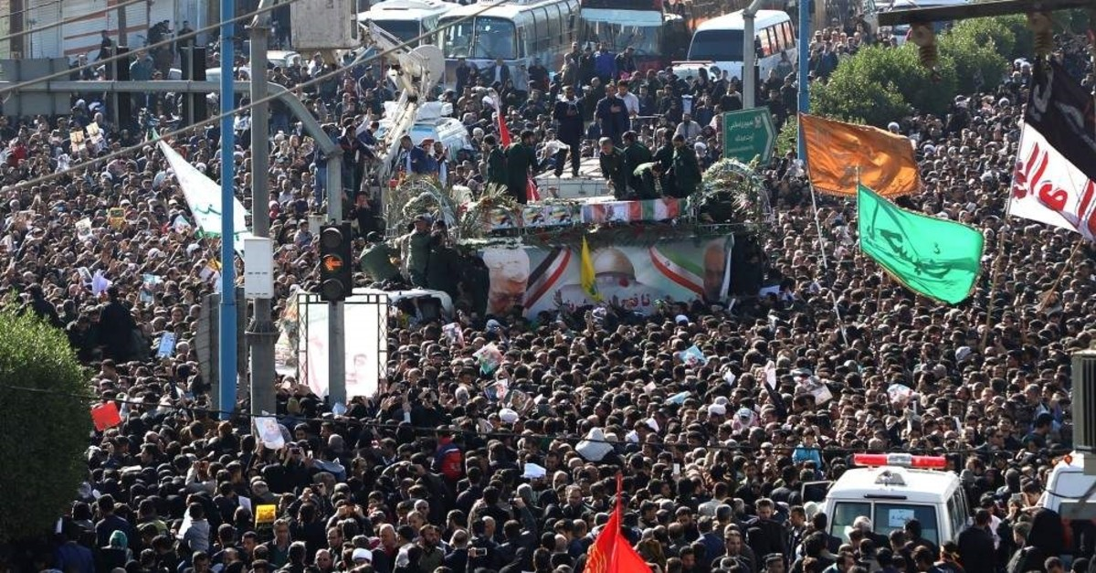 A large crowd surrounds the coffins of slain Gen. Qassem Soleimani and Iraqi paramilitary chief Abu Mahdi al-Muhandis, as they are transported atop a vehicle after their arrival at Ahvaz International Airport in southwestern Iran, Jan. 5, 2020. (Photo by Fars News / AFP)