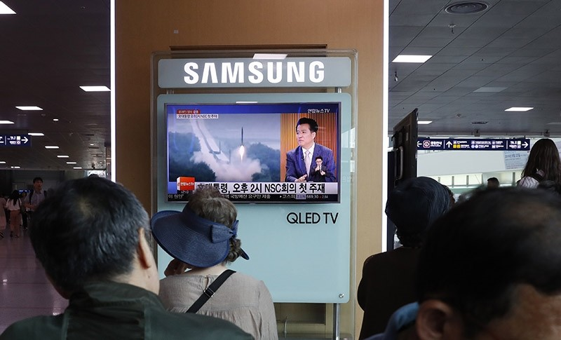 South Koreans watch a television broadcasting a news report on North Korea's recent missile launch at a station in Seoul, South Korea, 08 June (EPA Photo)