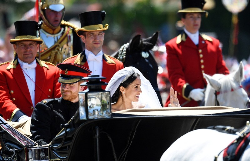 Britain's Prince Harry, Duke of Sussex and his wife Meghan, Duchess of Sussex ride in a horse-drawn Ascot Landau carriage along The Long Walk towards Windsor Castle during a procession after their royal wedding ceremony.