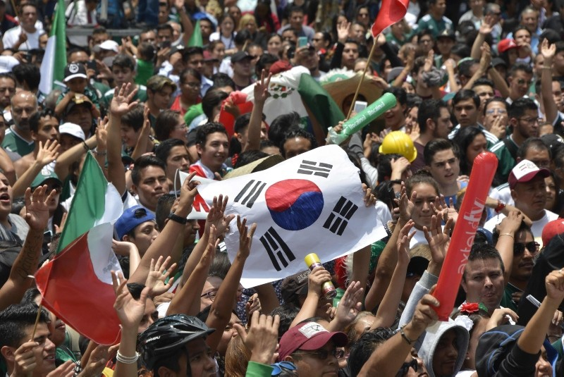 A football fan holds a flag of South Korea as thousands watch the World Cup match between Mexico and Sweden on a screen at the Angel de la Independencia Monument in Mexico City, June 27, 2018. (AFP Photo)