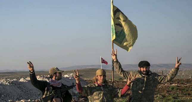 YPG terrorists pose with a banner with a picture of imprisoned PKK leader Abdullah Öcalan.