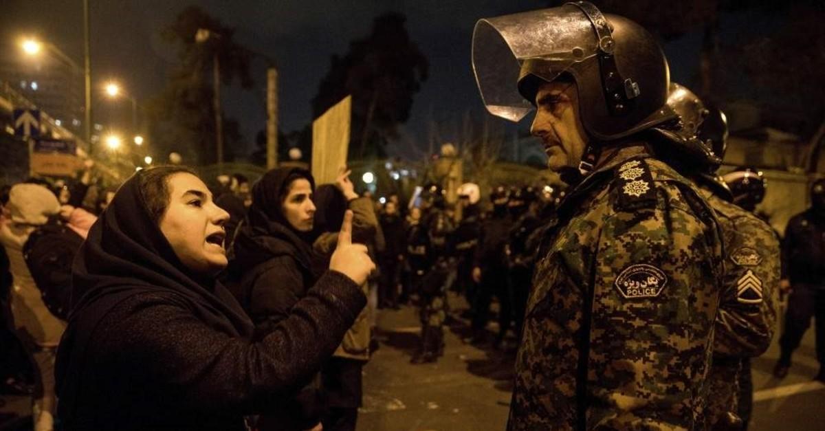 A woman talks to a policeman and asks for his sympathy at the gate of Amri Kabir University, Tehran, Jan. 11, 2020. (ISNA via AP)
