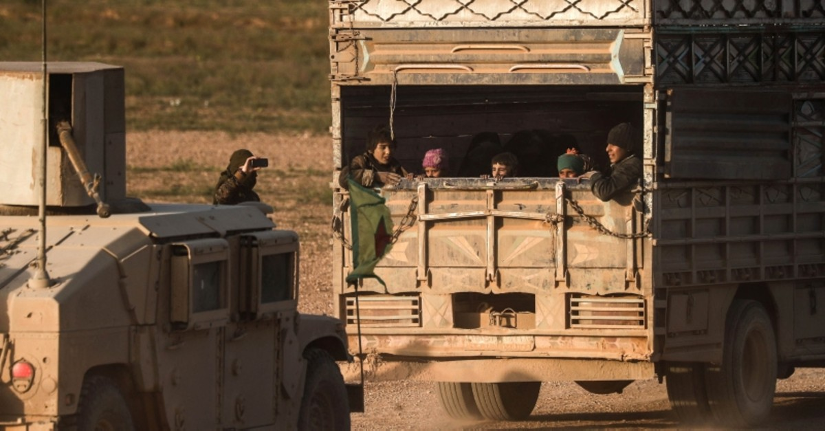 People evacuated from Daesh's embattled holdout of Baghouz sit in the back of a truck on Feb. 25, 2019 during an operation by the US-backed SDF in Syria. (AFP Photo)