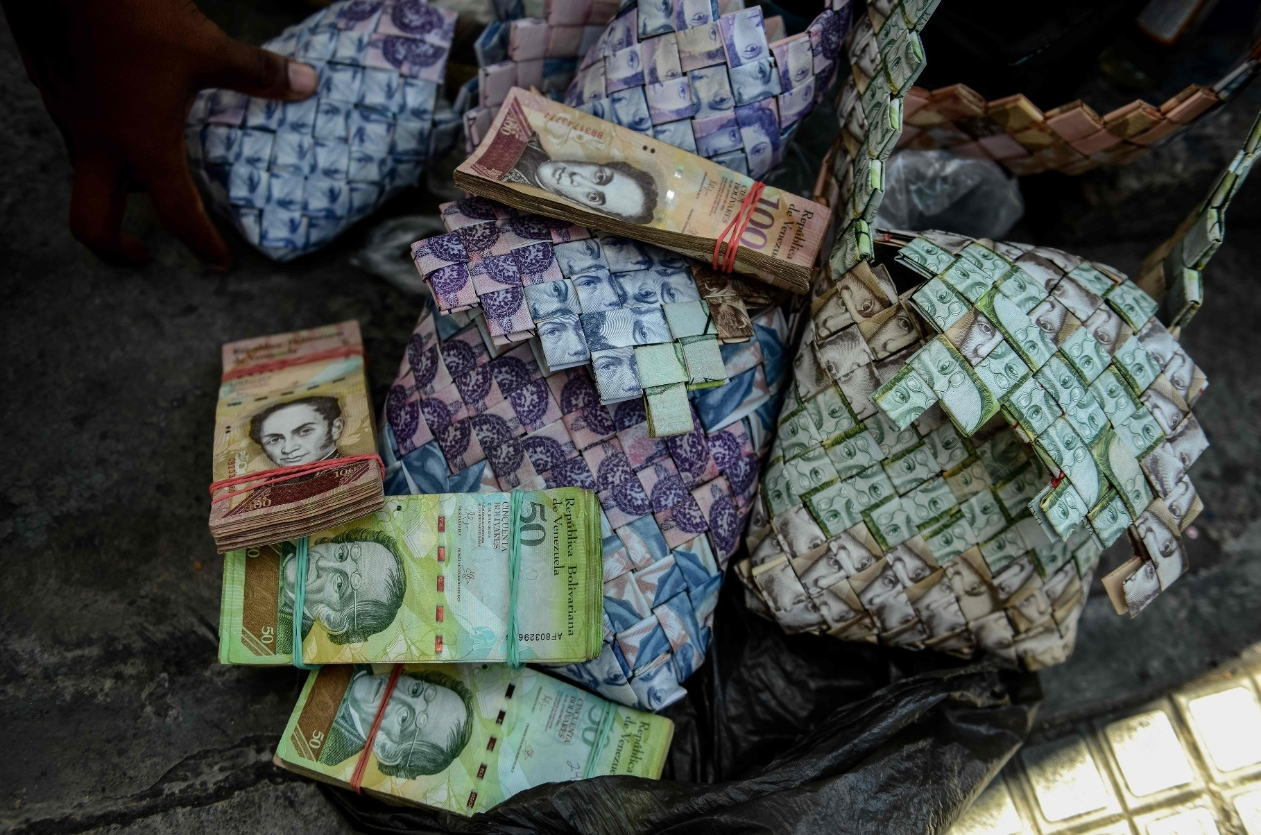 Wilmer Rojas, 25, shows the purses he makes, using Bolivar bills in Caracas.
