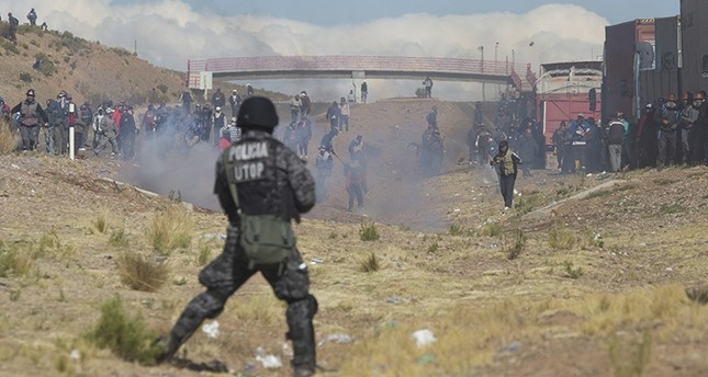 Independent miners clash with the police as they run from clouds of tear gas during protests in Panduro, Bolivia, Thursday, Aug. 25, 2016 (AP Photo)