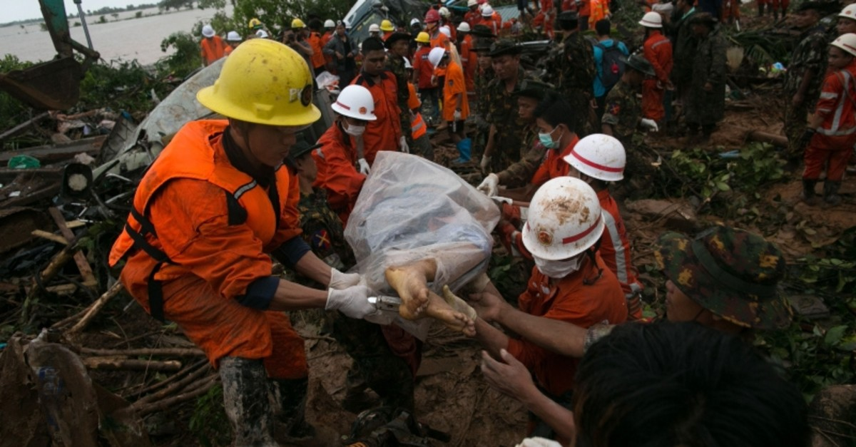 Rescue workers carry the body of a landslide victim in Paung township, Mon state on Aug. 10, 2019. (AFP Photo)