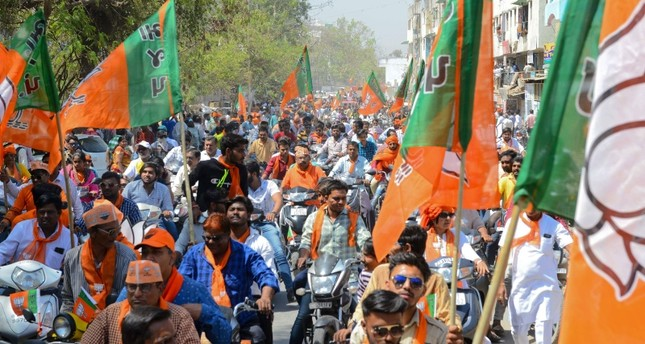 Indian Bharatiya Janta Party (BJP) supporters gather to follow BJP National President Amit Shah during his road show in Ahmedabad on April 6, 2019. (AFP Photo)