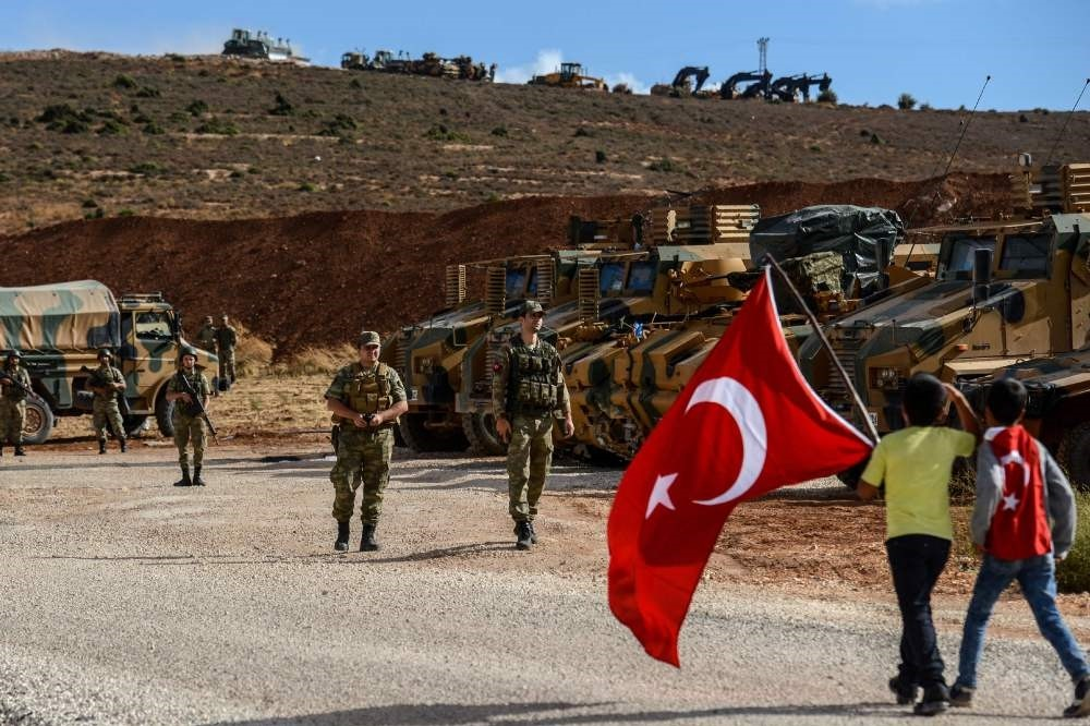 Turkish soldiers stand near armored vehicles as two boys holding Turkish flags arrive during a demonstration in support of the Turkish military's Idlib operation near the Turkish-Syrian border near Reyhanlu0131, Hatay, Oct. 10.