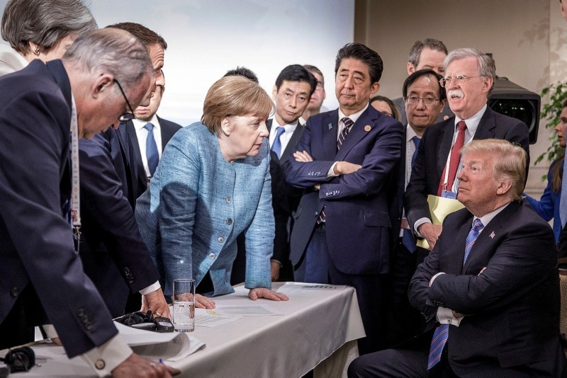 French President Emmanuel Macron (3-L, partially hidden), German Chancellor Angela Merkel (C-L) and Japan's Prime Minister Shinzo Abe (C-R) speaking to US Presidend Donald J. Trump (R, seated) during the G7 meeting in Canada. (EPA Photo)
