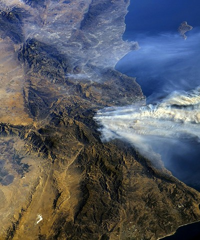 A photo taken from the International Space Station and moved on social media by astronaut Randy Bresnik shows smoke rising from wildfire burning in Southern California, U.S. on Dec. 6, 2017. (Reuters)