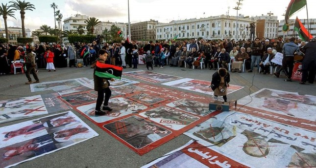 Portraits of Egyptian President Abdel Fattah al-Sisi, Saudi King Salman bin Abdulaziz, and Abu Dhabi Crown Prince Mohammed bin Zayed are displayed on the ground covered with red cross marks as people demonstrate against them and against eastern Libyan strongman Khalifa Haftar, and in support of the UN-recognized GNA in the Martyrs' Square in Tripoli, Dec. 27, 2019 AFP Photo