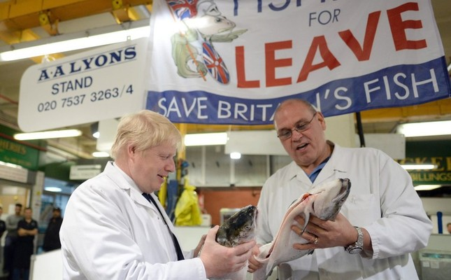 Former London Mayor Boris Johnson L with a worker as he visits Billingsgate Market, Britain's largest wholesale fish market, during a campaign event in London on Wednesday.