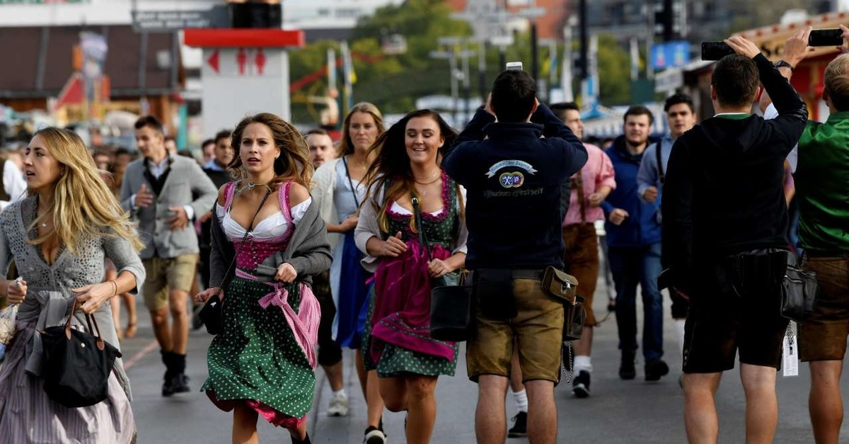 Visitors run to get a spot at the Oktoberfest area at the opening day of the 185th Oktoberfest in Munich, Germany September 22, 2018 (Reuters File Photo)