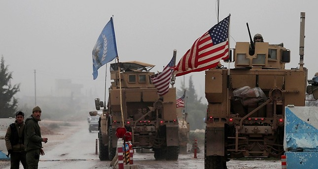 A line of US military vehicles drive through a checkpoint of the Internal Security Forces in Manbij as they head to their base on the outskirts of the northern Syrian city on Dec. 30, 2018 (AFP File Photo)