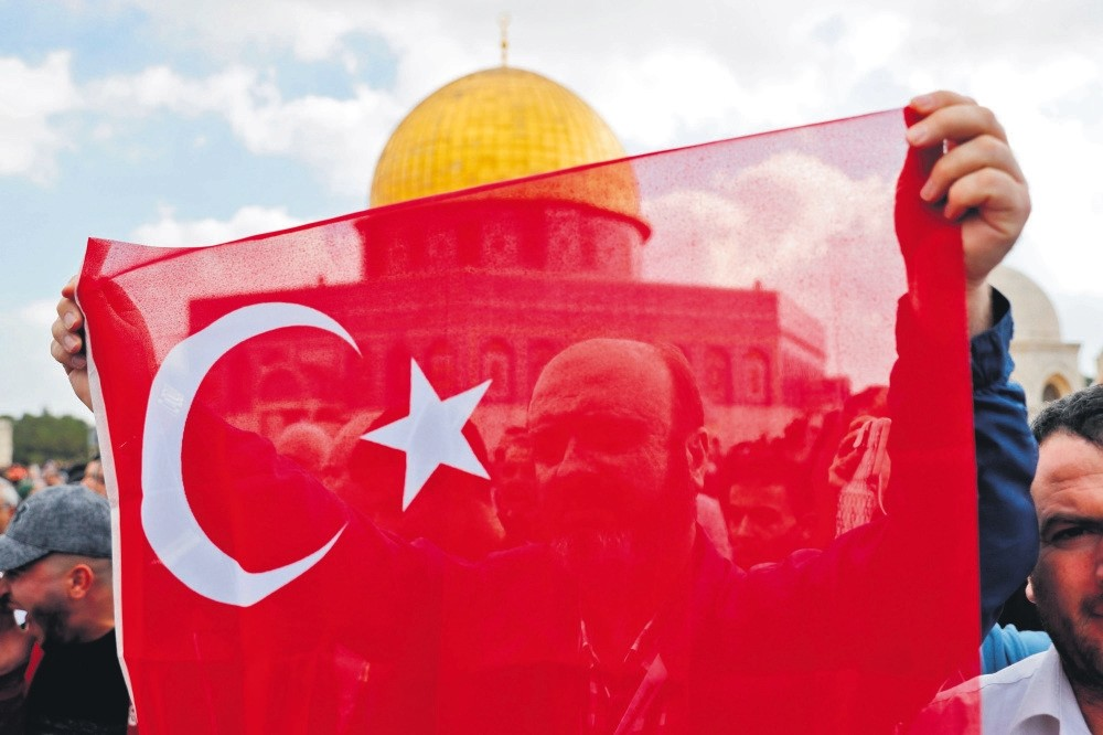 A MuslIm worshipper waves the Turkish flag in front of the Dome of the Rock at the Al-Aqsa Mosque compound in Jerusalem's Old City.