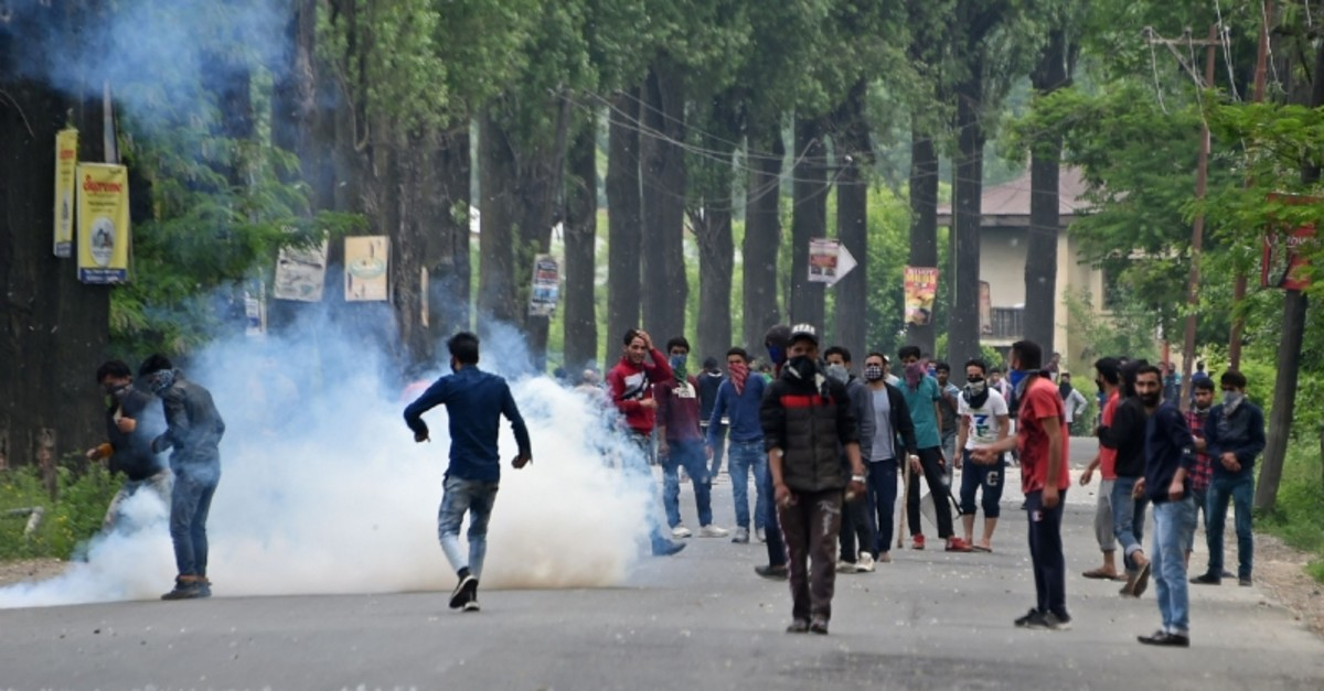Kashmiri protestors stand on a road amid tear smoke during clashes with Indian government forces at Mirgund Pattan on the outskirts of Srinagar on May 13, 2019. (AFP Photo)