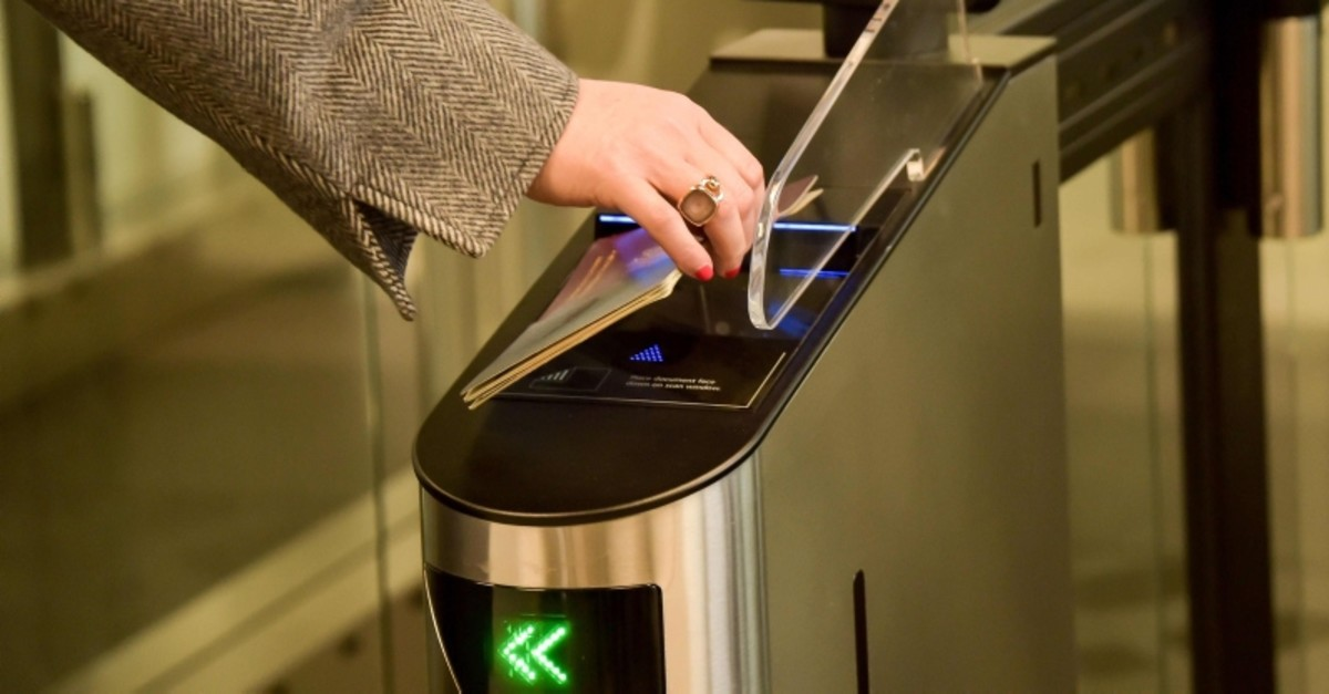 A woman scans her passport at an automated kiosk on March 28, 2019 at the Coquelles border post, a new border inspection post for customs and sanitary control built in anticipation of a no-deal Brexit. (AFP Photo)