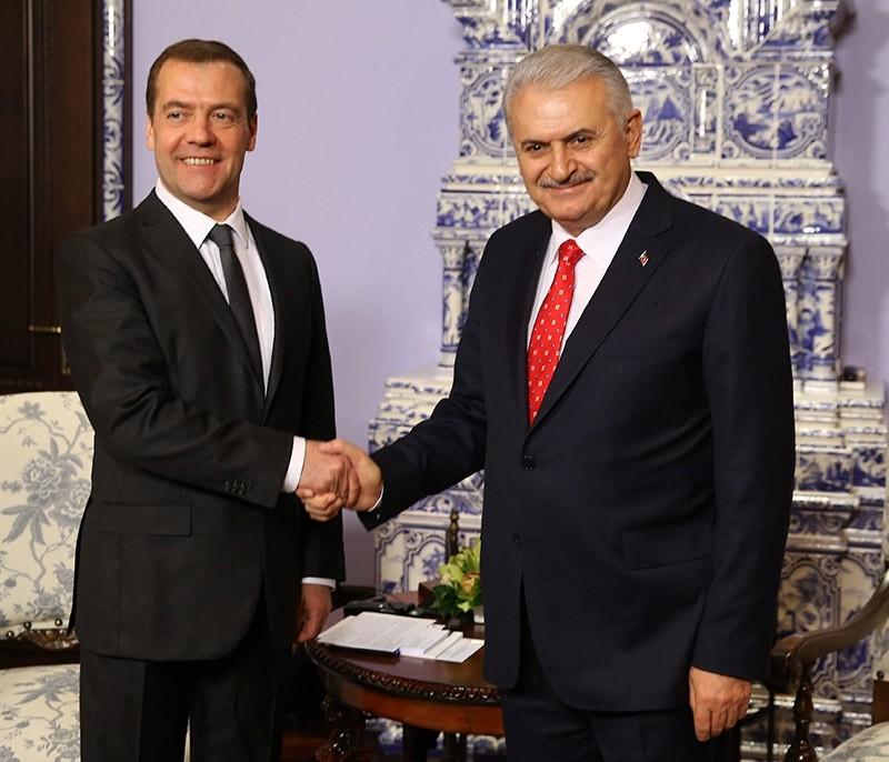 Turkish PM Binali Yu0131ldu0131ru0131m (R) shakes the hand of his Russian counterpart Dmitry Medvedev. (File Photo)