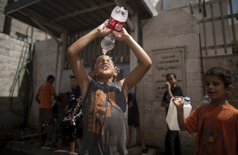 Two Gazan boys try to cool off by pouring bottles of water over their heads.
