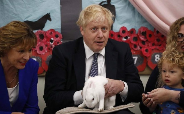 Britain's Prime Minister Boris Johnson holds Rosie the rabbit during a visit to the West Monkton CEVC Primary School on his general election campaign trail, Taunton, Nov. 14, 2019. (AP Photo)