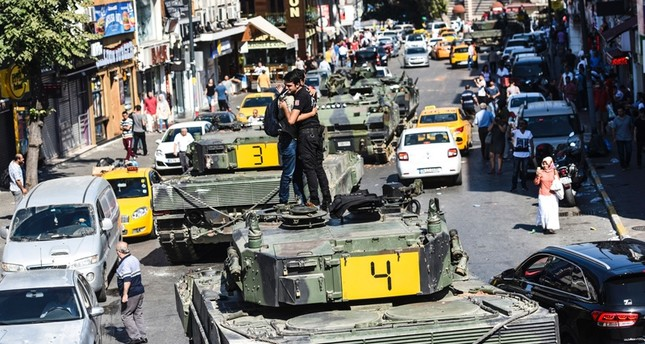 Turkish police officer (R) embrace a man on a tank after the military position was taken over in Istanbul on July 16, 2016.emAFP Photo/em