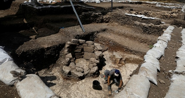 A man works next to a burial place at an excavation site where a huge prehistoric settlement was discovered by Israeli archaeologists in the town of Motza near Jerusalem (Reuters Photo)