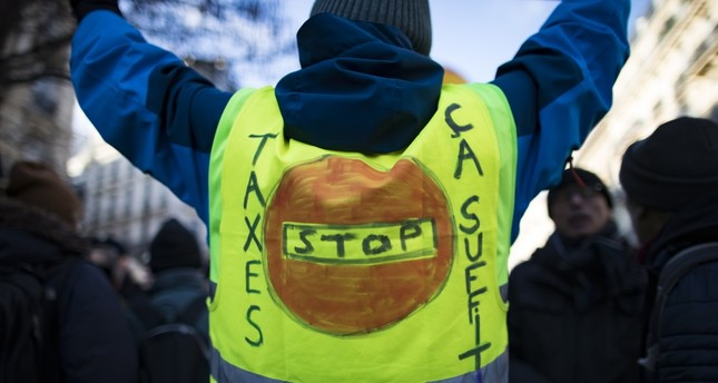A yellow vest bears the message 'Stop Taxes' as high school students and union workers take part in a demonstration for pensions and social conditions, Paris, France, Friday.