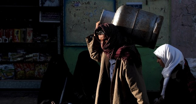 A Yemeni carries an empty cooking gas cylinder as he looks for gas supplies at a street amid increasing cooking gas shortages, Sanaa, Nov. 28.