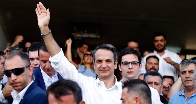 Greek opposition New Democracy conservative party leader Kyriakos Mitsotakis waves to his supporters outside of a polling station in Athens, on Sunday, July 7, 2019. (AP Photo)