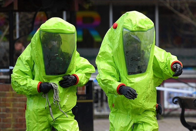 In this file photo taken on March 8, 2018 members of the emergency services in green biohazard encapsulated suits work to afix the tent over the bench where Sergei and Yulia Skripal were found in critical condition in Salisbury. (AFP Photo)