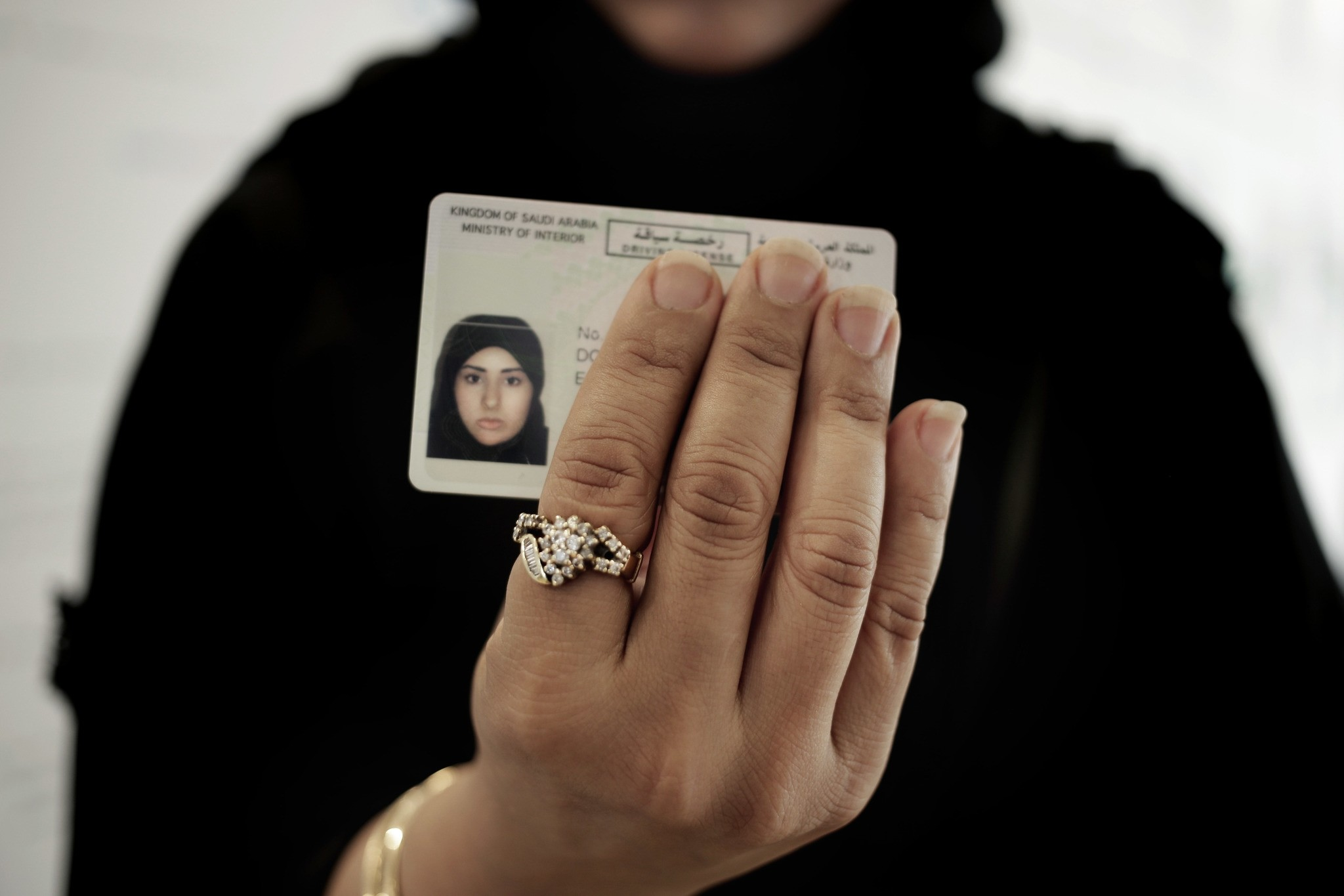In this June 23, 2018 photo, a Saudi woman covering her name holds her new car license at the Saudi Driving School inside Princess Nora University in Saudi Arabia. (AP Photo)