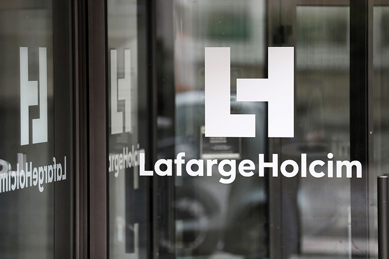 This file photo taken on March 9, 2017 in Paris shows a logo at an entrance of the French headquarters of LafargeHolcim, a group created in 2015 by the merger of French cement manufacturer Lafarge and its Swiss counterpart Holcim. (AFP Photo)