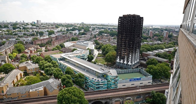 Railway tracks run in front of the charred remains of the Grenfell Tower block in Kensington, west London, on June 17, following the June 14 fire at the residential building. (AFP Photo)
