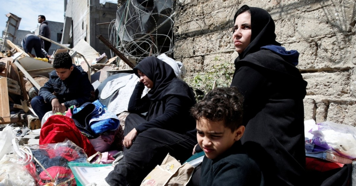 Palestinians sit with their belongings in a street outside their destroyed house after an Israeli missile targeted a nearby Hamas site, in Gaza City March 26, 2019. (Reuters Photo)