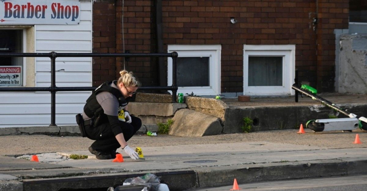 A Baltimore police forensics officer places an evidence marker next to a bullet casing while investigating the scene of a shooting in Baltimore. (AP Photo)