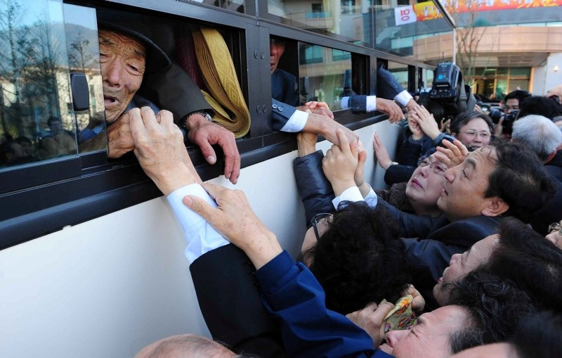 In a file picture taken on November 1, 2010 North Koreans (in the bus) grip hands of their South Korean relatives as they bid farewell following their family reunion meeting at Northu2019s Mount Kumgang resort, near the border. (AFP Photo)