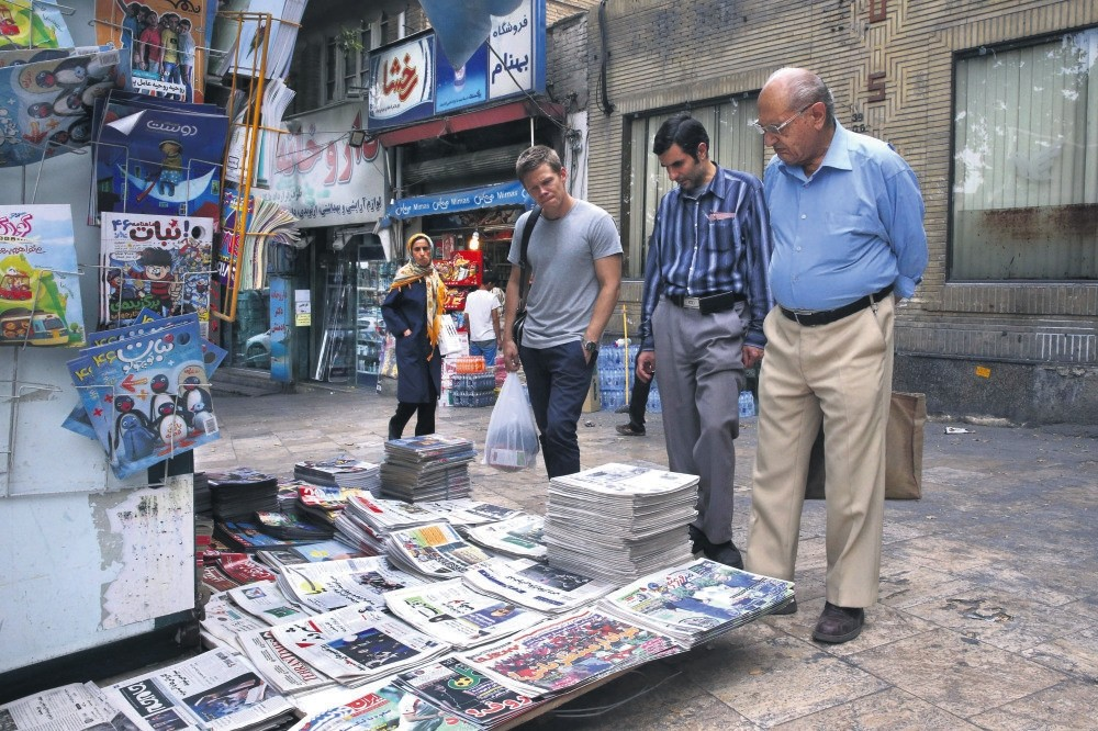 People reading the headlines of Iranian newspapers at a newsstand, in Tajrish Square, Tehran, July 7, 2015.