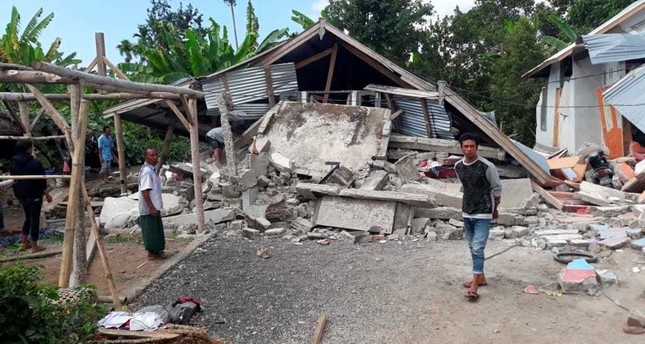 Villagers walk near destroyed homes in an area affected by the early morning earthquake at Sajang village, Sembalun, East Lombok, Indonesia, Sunday, July 29, 2018. (AP Photo)
